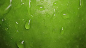 Drops of water flow down along the surface of a green apple stock video