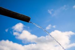 Drops of water flowing from pipe - close up with blue sky. Concept for water shortage and environmental issues. Copy space. For writing royalty free stock photography
