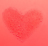 Drops of water in the form of heart on a red background Stock Images