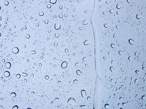 Drops of water on glass in cool tone for wallpaper texture background. stock photo