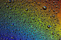 Drops of water on the glass, with the reflection of the rainbow. Background stock photo