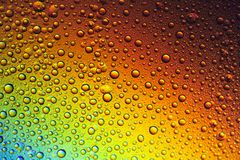 Drops of water on the glass, with the reflection of the rainbow. Background royalty free stock photography
