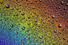 Drops of water on the glass, with the reflection of the rainbow. Background royalty free stock photo