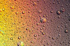 Drops of water on the glass, with the reflection of the rainbow. Background stock photos