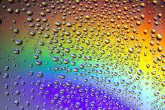 Drops of water on the glass, with the reflection of the rainbow. Background stock image