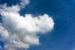 Drops of water on glass window over blue sky Royalty Free Stock Image