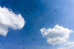 Drops of water on glass window over blue sky Royalty Free Stock Images