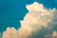 Drops of water on glass window over blue sky. Royalty Free Stock Photos