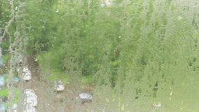 Drops of water, like lenses, on mosquito net. Summer pouring rain in city. 4K video