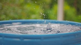 Drops of water from the roof fall into a blue barrel