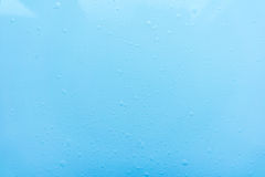 Drops, water splashes on blue background. Cute simple background, backdrop. Top view. Close-up. Stock photo Stock Image