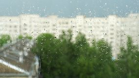 Drops of water on the window glass. Summer rain in city, blurry silhouettes of houses and green trees. 4K video