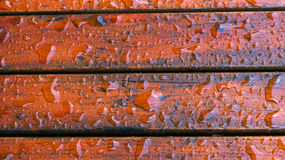 Drops of water on wood. Close up details of drops of water on red wood stock image