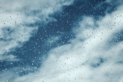 Drops on window, blue sky with clouds on background Stock Photos