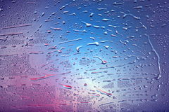 Drops on window. Different colors. Violet and blue Royalty Free Stock Photos