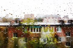 Drops on the window glass. Drops of water on the window glass. Behind the glass silhouettes of buildings with windows royalty free stock images