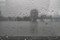 Drops on window pane. Blurred cityscape seen through rain drops on wet window pane royalty free stock photo