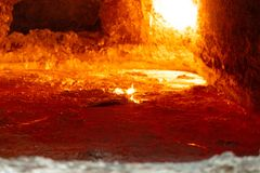 Dross layer on liquid aluminum. Looking inside an aluminum melting furnace, in a foundry, with liquid metal and the oxidize dross layer on it stock photos