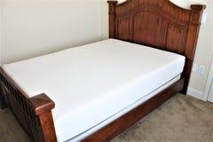 Drottning storleksanpassad säng som är ogjord i ett sovrum med en skummadrass Arkivfoto
