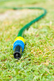 Drought. Gardening water pipe lying and dripping a drops of water to dry ground druing hot summer Stock Image