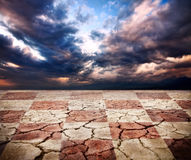 Drought earth with chess desk texture. At storm dramatic sky background royalty free stock photos