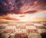 Drought earth with chess desk texture. At storm dramatic sky background royalty free stock images