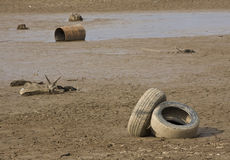 Drought Exposure. A long term drought in Atlanta exposes dirt and debris in a dry lake bed of red clay.  Focus is on the tires Royalty Free Stock Photography