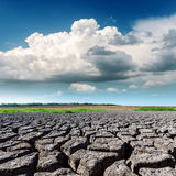 Drought land and low clouds in blue sky Royalty Free Stock Photo