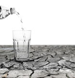 Drought relief. Water being poured out from a mineral water bottle into a crystal glass sitting on a drought stricken dry cracking mud surface with blank space stock photos