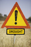 Drought warning. Red warning triangle and the word drought in dry grassland, environmental concept for climate change, Botswana, Africa royalty free stock photo