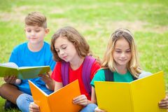 Droup of children reading books at the park Royalty Free Stock Photography