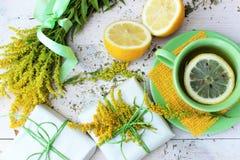 Droup der gelben und grünen Frucht und der Anlagen auf weißem hölzernem Hintergrund Lizenzfreies Stockbild