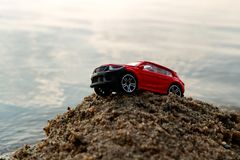 Drove on a pile of sand red car on the background of the sea, a Sunny day in the summer. The sea journey by car stock photography
