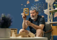 Old bearded man with alzheimer desease. Drown image of losing of mind. Old bearded man with alzheimer desease has problems with his hands motor skills. Illness stock photo