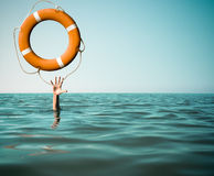 Drown man with rised hand getting lifebuoy help in sea Stock Photography