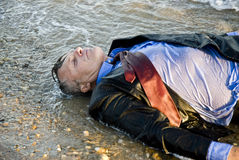 Drowned businessman. Color photo of a drowned forties businessman laying on the sea shore Royalty Free Stock Images