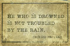 Drowned CP. He who is drowned is not troubled by the rain - ancient Chinese proverb printed on grunge vintage cardboard stock photo