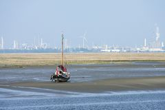 Drowned Land of Saeftinghe. Boat at low tide at Drowned Land of Saeftinghe with industrial area in background stock photos