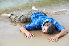 Drowned man. Drowned dressed man lying on sea shore at tide stock image