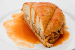 Drowned Pork Sandwich. Mexican Torta Ahogada, or drowned sandwich with pork on a white plate Royalty Free Stock Images