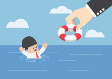 Drowning businessman getting lifebuoy from big hand Royalty Free Stock Photo
