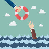 Drowning businessman getting lifebuoy from other businessman Royalty Free Stock Photography