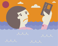 Drowning on credit card debt. Businessman sinks into the ocean as he holds a credit card Stock Photo
