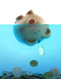 Drowning in debt. Represented by a piggy bank sinking in blue water stock image