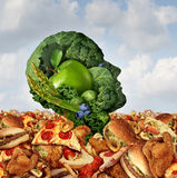 Drowning In Fat. Concept as a human face made of fresh green vegetables and fruit struggling to survive from the ocean of greasy fast food and fried foods as a Stock Photo