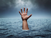 Drowning hand in stormy sea Stock Image