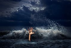 Drowning man hand in storm sea water stock photography