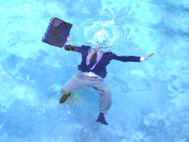 Drowning Not Waving. Business man with briefcase drowns in blue water Royalty Free Stock Image