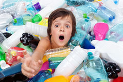 Drowning in the plastic flood. Boy reaching out for help from the overflowing garbage Royalty Free Stock Photography