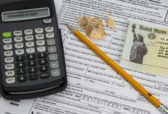Drowning in Tax Debt. Tax time with tax forms and sinking and drowning in debt with small social security checks or Disability Check SSI. Individual Tax Return royalty free stock photos